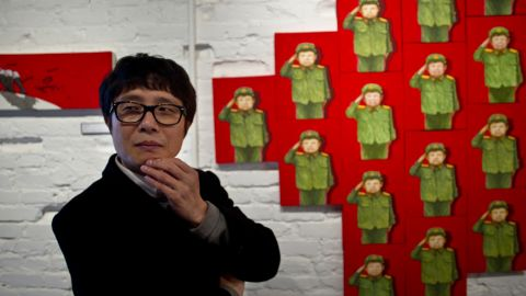 """Song Byeok's paintings are often about coming to terms with life outside North Korea. Behind him is the painting """"Child Warrior,"""" depicting the curious North Korean custom of dressing children in military clothes on special birthdays. Song painted the boy with his eyes closed."""