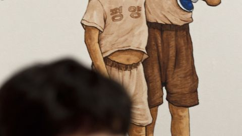 """Like most North Korean families, Song's parents didn't want him to wear his shoes unless it was necessary. """"Shoes cost parents three or four days' wages,"""" Song said, """"and children were expected to stitch their own repairs."""" In """"Barefoot Boys,"""" a T-shirt says """"Nothing to Envy in the World."""""""