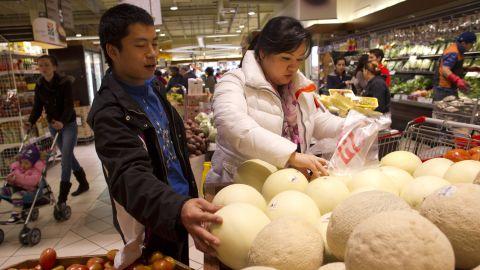 JinHye and her friend, Jacob Seo, also a North Korean defector, pick melons at a Korean supermarket. North Korean defectors form a small community in the D.C. area.