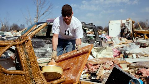 Douglas Osman sifts through the wreckage of his grandmother's house Wednesday in Harrisburg. His grandmother, Mary Osman, was one of six people killed in the Illinois town.
