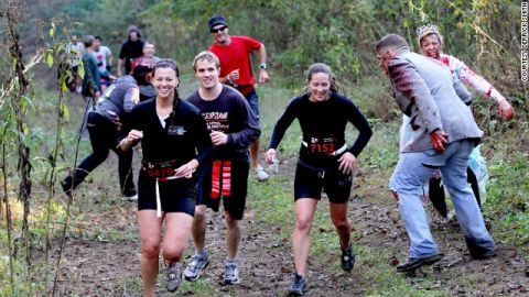 """Runners swerve around some zombies at the 2011 """"Run For Your Lives"""" event in Darlington, Maryland."""