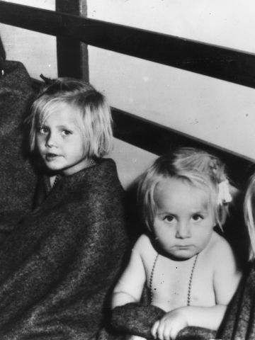 The revolution also created tens of thousands of refugees. Here, a woman and her three children arrive in Swtizerland after her husband was killed fighting the Soviet forces.