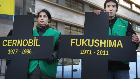 """Greenpeace activists hold black crosses. one reading """"Fukushima"""" nuclear power plant and the other, """"Chernobyl,"""" at a protest in Bucharest March 5."""