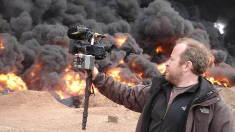 CNN senior photojournalist Neil Hallsworth films an oil fire in Homs, Syria.