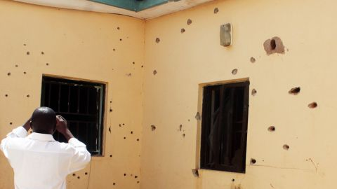 A man takes photos Friday of a bullet-riddled wall at the scene of the failed rescue operation in Nigeria.