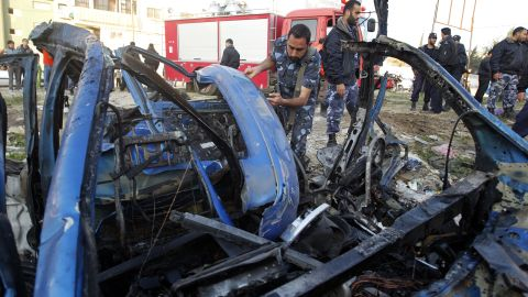 A Hamas policeman inspects the remains of a vehicle that was targeted by an Israeli airstrike in Gaza City.