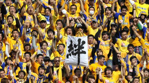 """Vegalta Sendai's fans hold up a banner reading """"Bond"""" to show the close support they have for their team"""
