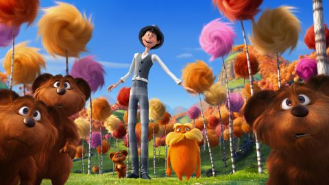 This still from the 2012 animated film shows the orange Lorax character in the center surrounded by colorful Truffula trees.