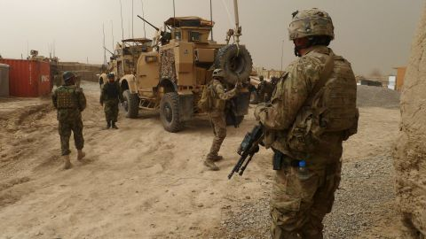U.S. soldiers keep watch at the entrance of a military base near Alkozai on Sunday, following the shooting of Afghan civilians.