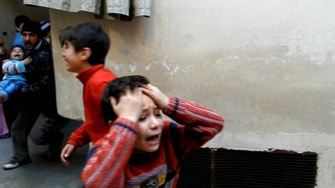 A man (L) runs carrying a toddler as children weep during fighting in Homs, on February 25, 2012.