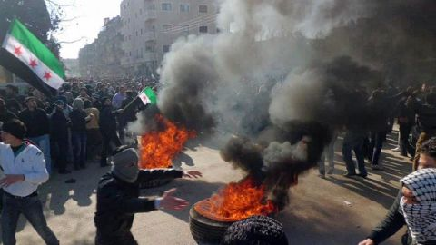 Syrian protesters burn tires and wave independence flags during an anti-regime demonstration in the Damascus suburb city of Daraya on February 4, 2012
