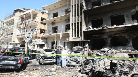 Syrian security officers inspects the scene at a destroyed building following twin bomb attacks in Damascus on Saturday.