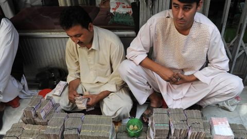Afghani money changers count afghani bank notes at the exchange market in downtown Kabul on August 10, 2011
