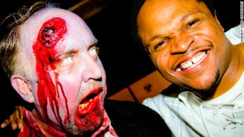 """""""Walking Dead"""" actor IronE Singleton (right) hangs out with a surprised zombie at the Diesel Filling Station finale party."""