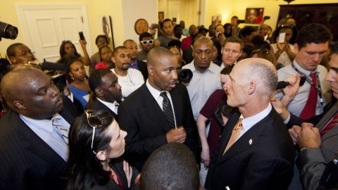Tallahassee defense attorney Deveron Brown talks to Florida Gov. Rick Scott, right, about the shooting of Trayvon Martin.