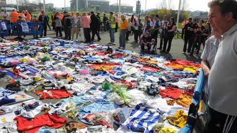 Fans of Bolton Wanderers and a host of other football clubs lay shirts outside of the Reebok Stadium in a show of support for Fabrice Muamba.