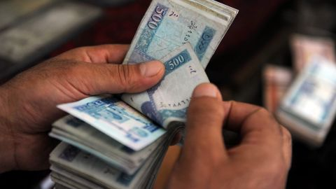 An Afghan money changer counts afghani bank notes at the exchange market in Kabul on August 10, 2011.