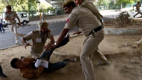 Police detain a Tibetan activist protesting outside the Oberoi Hotel in New Delhi on March 28, 2012.