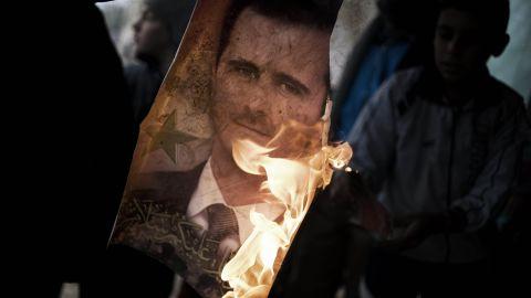 A Free Syrian Army member burns a portrait of President Bashar al-Assad, southwest of Homs, on January 25.