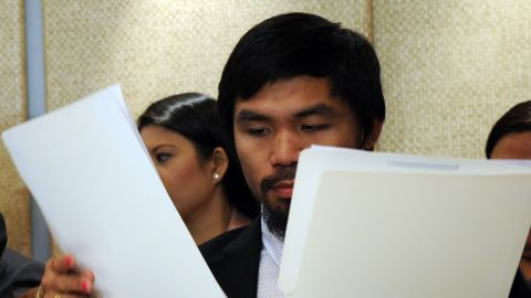 Pacquiao examines documents given to him by an aide, during a press conference in Manila on March 26, 2012.