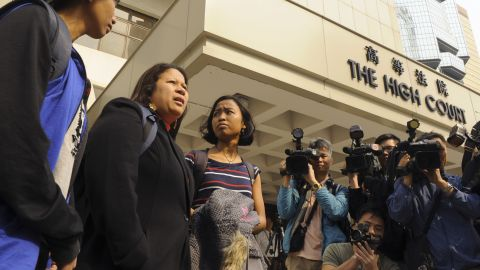 Asian Migrants' Coordinating Body reps stand outside of the High Court in Hong Kong on March 28, 2012.