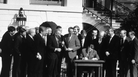 President Ronald Reagan signs the Tax Reform Act in October 1986, with congressional leaders joining in the ceremony.