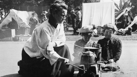 A refugee from the 1906 San Francisco earthquake prepares a meal over a makeshift stove at the  Army-run Golden Gate Park relief camp. In the background, soldiers and other refugees stand near tents set up for living quarters. An estimated 225,000 people were left homeless after the earthquake and subsequent fires.