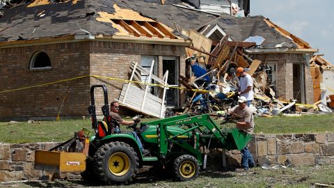 Volunteers use a small tractor to clear debris in front of a damaged house.