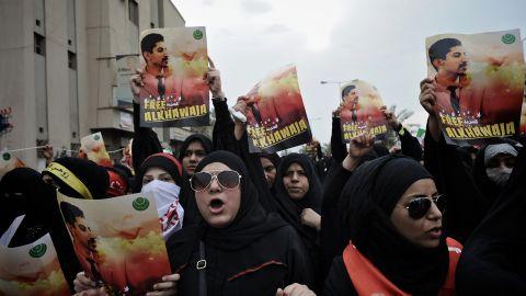 Bahraini Shiite demonstrators hold posters of jailed activist Abdulhadi al-Khawaja during a protest Friday.