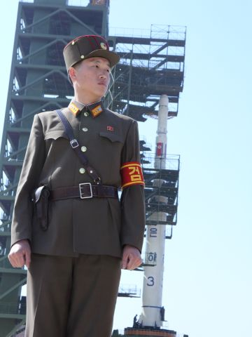 A North Korean soldier stands guard in front of the Unha-3 rocket during a media tour of the Sohae Satellite Launching Station on April 8, 2012.