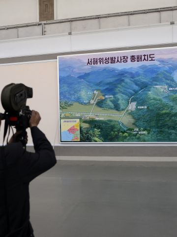 A North Korean cameraman films a map showing the site where the Unah-3 rocket is being prepared for launch.