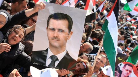 A Syrian woman holds a picture of President Bashar al-Assad as other protestors fly Palestinian and pre-Baath Syrian flags during a demonstration to mark Land Day in Damascus on March 30, 2012.