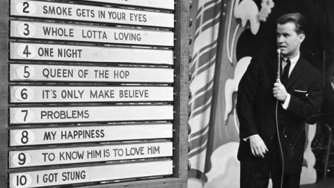 circa 1958:  American TV show host Dick Clark anounces the week's top ten popular songs during an episode of the television program, 'American Bandstand.'  (Photo by Hulton Archive/Getty Images)