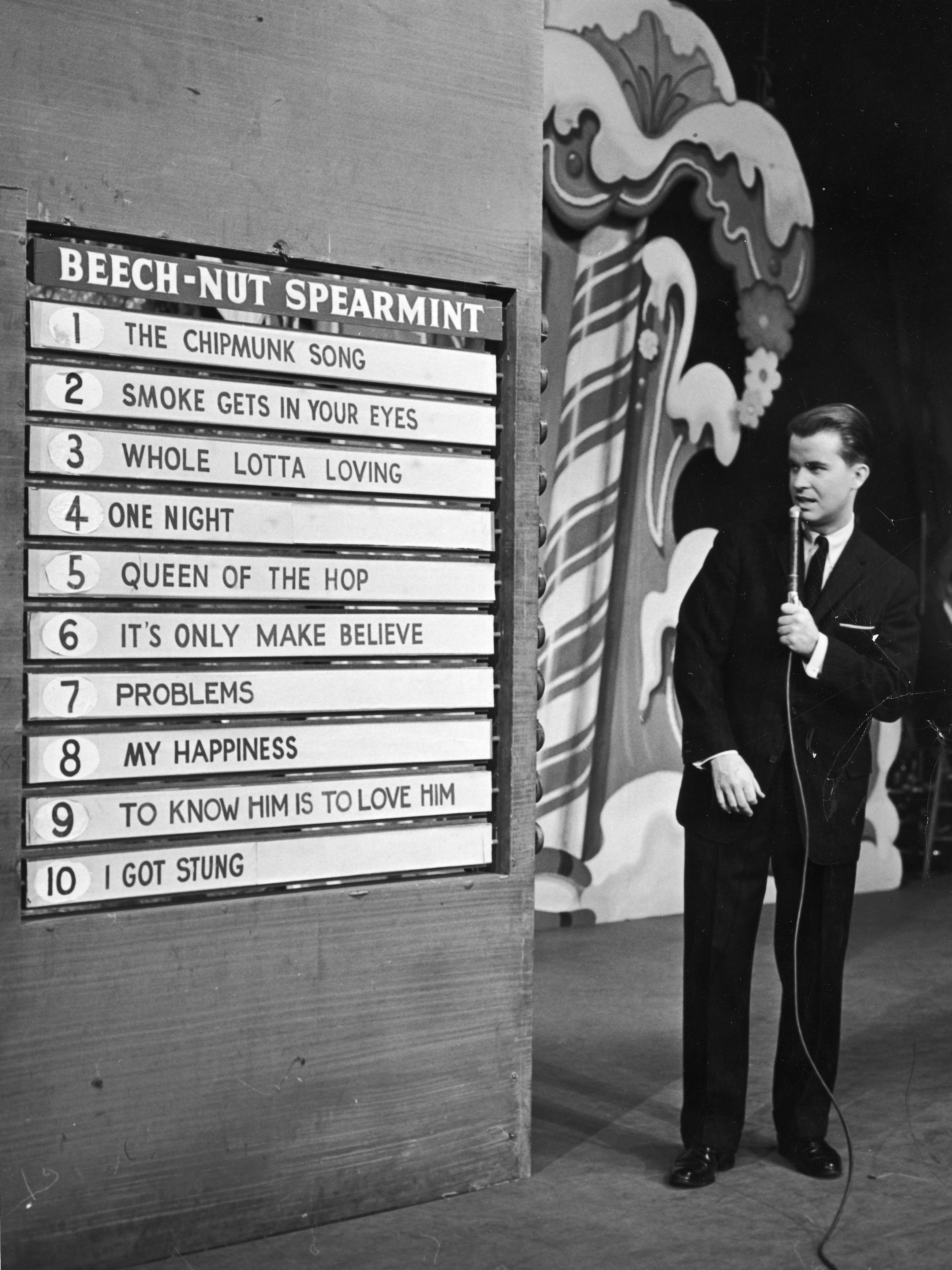 """Clark announces the week's top 10 popular songs during an episode of the TV show, """"American Bandstand,"""" circa 1958."""