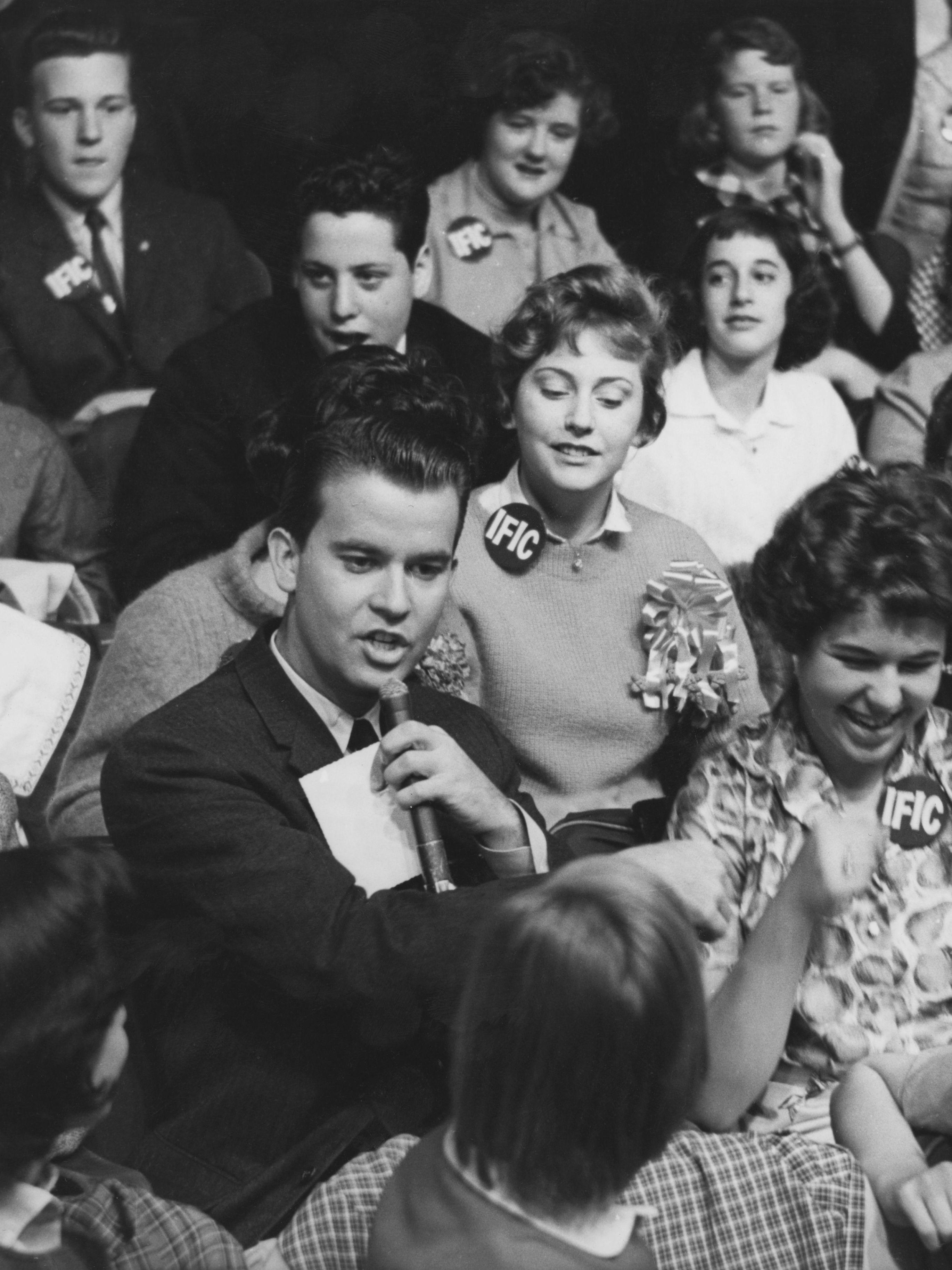 """""""American Bandstand"""" host Clark, pictured in 1958, surrounded by audience members."""