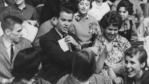 """""""American Bandstand""""  host Dick Clark, pictured in 1958, surrounded by audience members."""