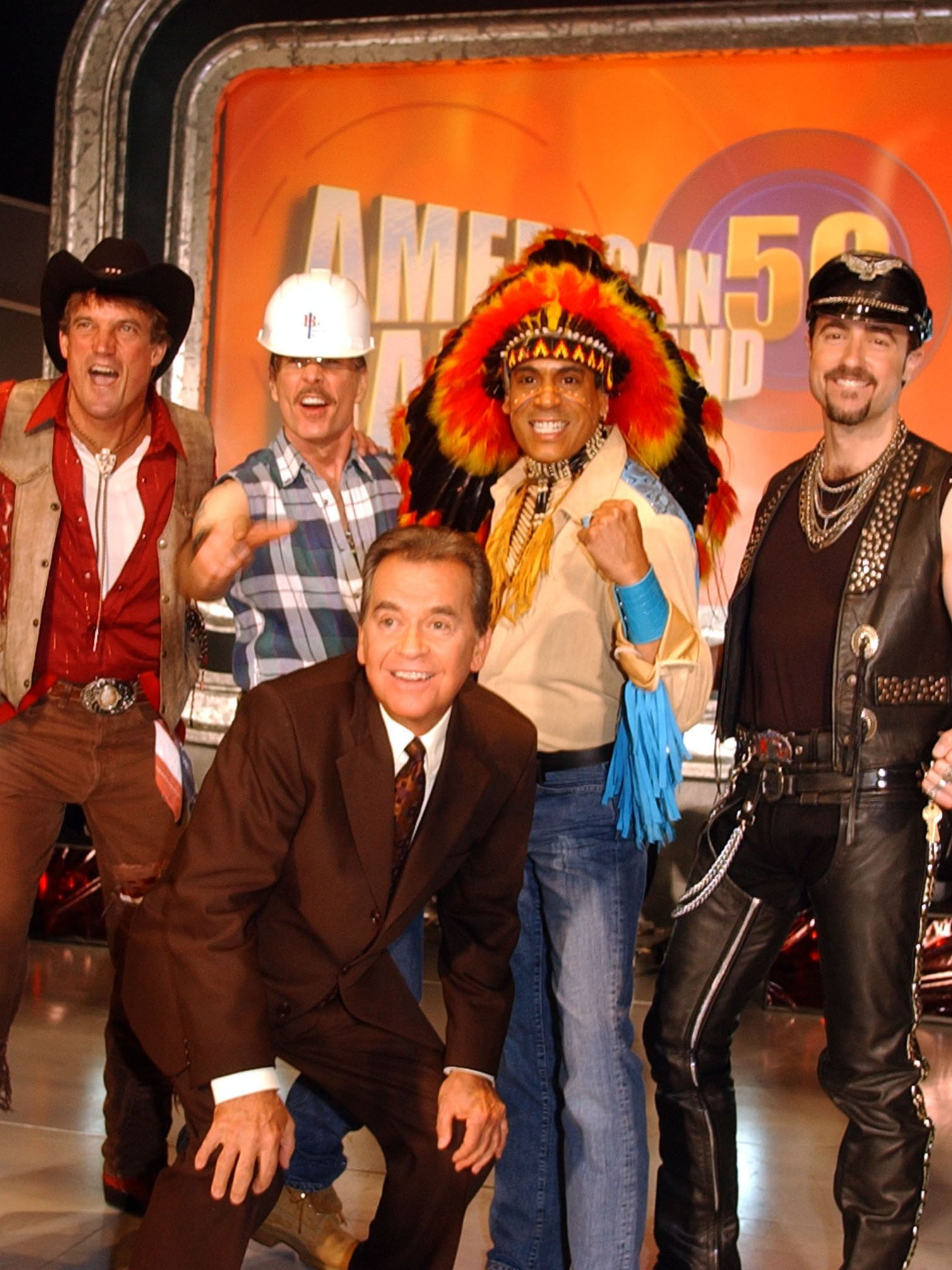 """Clark poses with """"The Villiage People"""" at the taping of the 50th anniversary special of """"American Bandstand."""""""