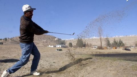 An Afghan player takes a swing during a tournament at the Kabul Golf Club. The nine-hole course, which first opened in 1967, became a battlefield in the 1990s when rival Mujahideen factions fought among themselves after overthrowing a Soviet-backed regime.