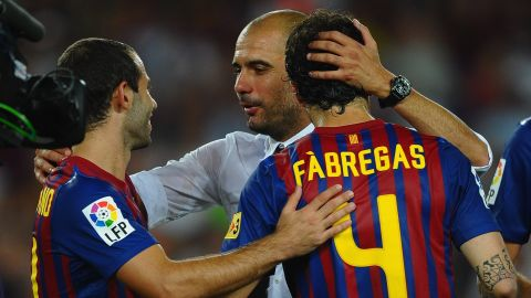 Guardiola congratulates Barca players Cesc Fabregas and Javier Mascherano after winning the Spanish Supercup against Real Madrid at the start of the 2011-12 season.