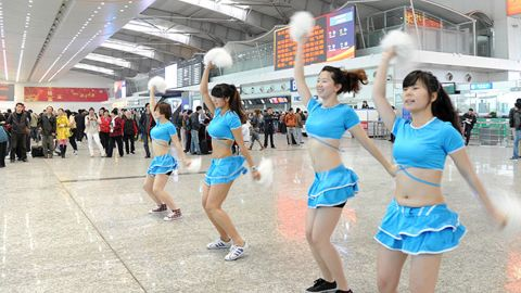 To entertain waiting passengers, Dalian International Airport uses cheerleaders. Speculation is growing that China will spend more on infrastructure projects to stimulate the slowing economy.