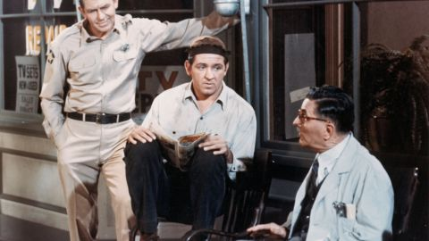 """Andy Griffith, left, Lindsey, center, and Howard McNear talk outside a barber shop in a still from """"The Andy Griffith Show"""" around 1966."""