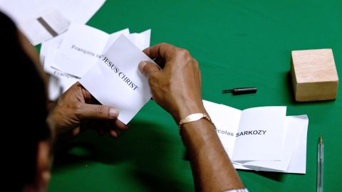 """In South America, a scrutineer unfolds a ballot for """"Jesus Christ"""" as he counts votes in French Guiana's Remire-Montjoly."""