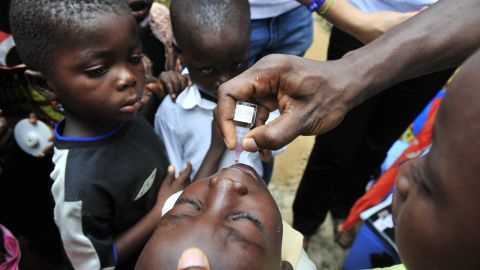 A child receives an oral polio vaccine in Ivory Coast. Improved vaccines are helping save children's lives globally.