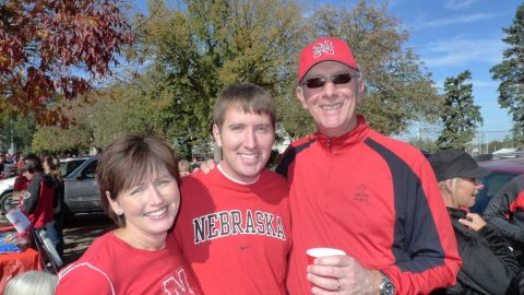 Brett Major, center, with his parents, is a gay Christian Nebraska fan who once revered Brown.
