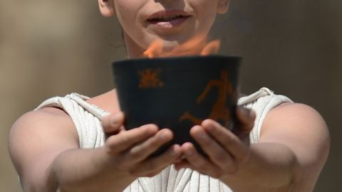 """The priestess, played by Greek actress Ino Menegaki, lifts the """"Archaic Pot"""" from which the flame is lit."""