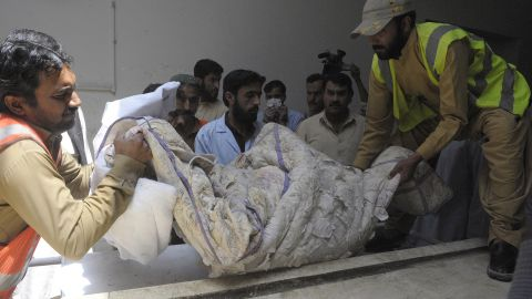 Pakistani volunteers carry the body of British aid worker Khalil Rasjed Dale at a hospital in Quetta on April 29.