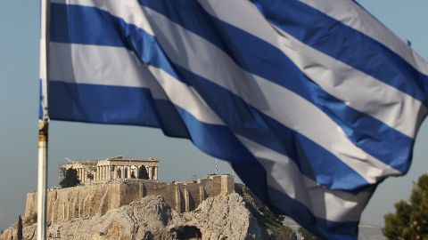 The Greek flag flies in front of the Acropolis