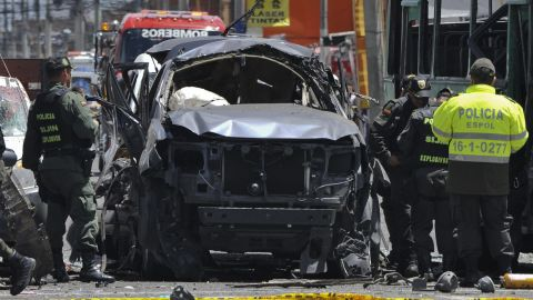 Police officers inspect the car of former Interior and Justice Minister Fernando Londono on Tuesday in Bogota.