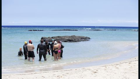 The Fit Nation team receives more instructions before their first open-water swim.