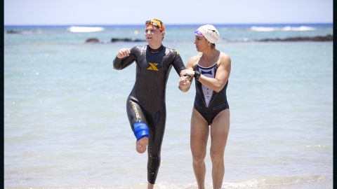 Roni Selig, Fit Nation coach and director of the CNN Medical Unit, helps Castelli out of the water.